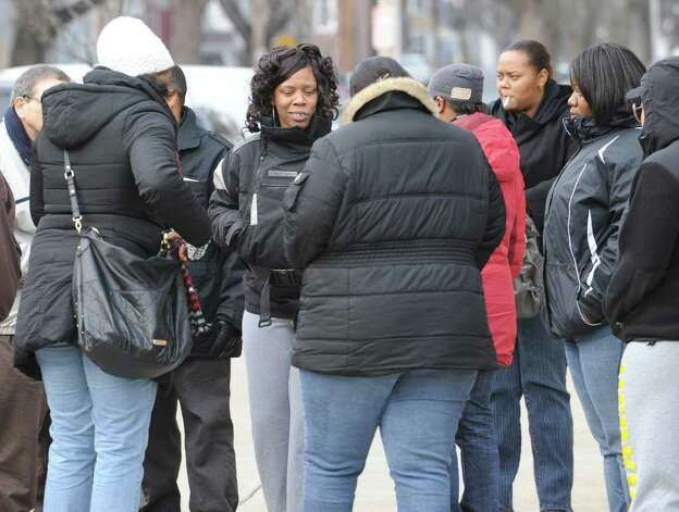 Davina Woodard, center facing camera, mother of shooting victim, gets consoled by family and friends after community group members talked outside the Public Safety Building on Henry Johnson Blvd about the overnight police shooting that left her son dead Friday, Dec. 30, 2011 in Albany, N.Y. (Lori Van Buren / Times Union) Photo: Lori Van Buren