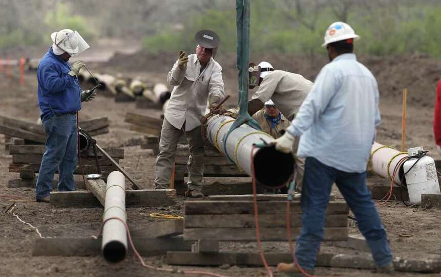 Welding crews are busy laying pipelines such as this one east of Karnes City, Texas in order to get
