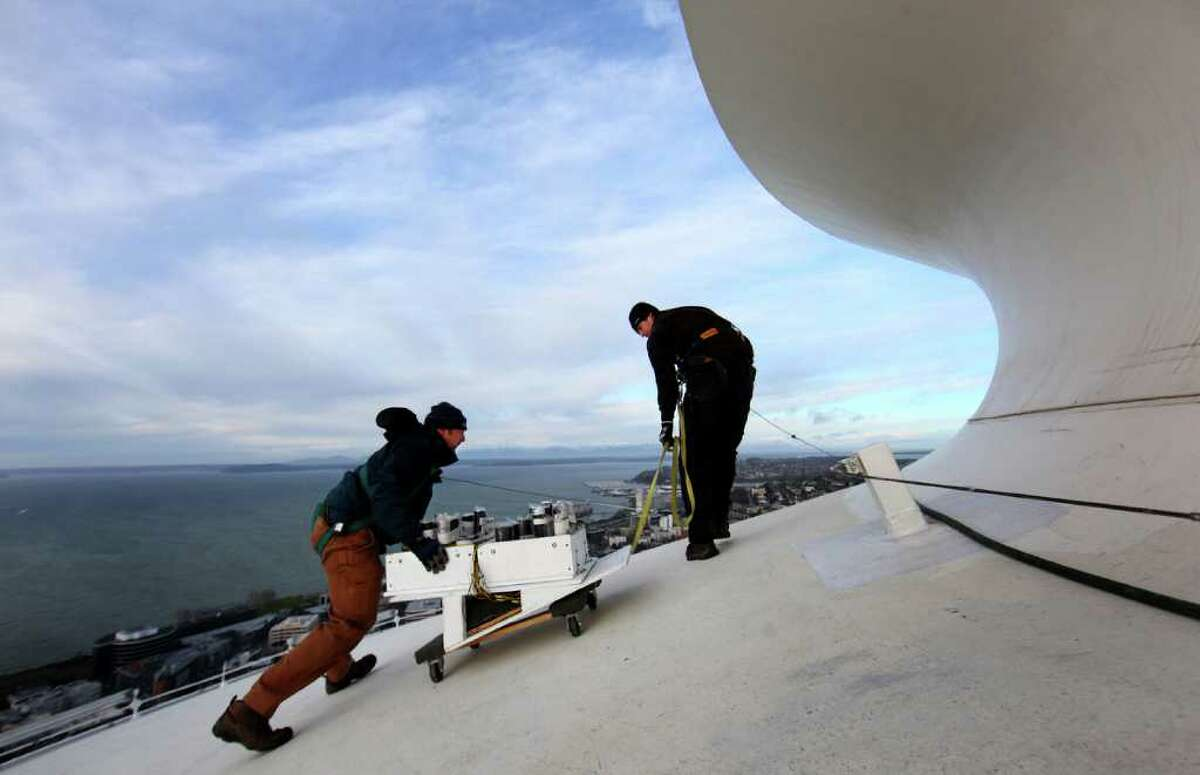 Scott Streeper, left, and Matt Gilfillan prepare to place fireworks on the roof of the Space Needle as a crew prepares for the annual New Years firework display. The crew started placing fireworks on the iconic Seattle landmark on Wednesday, December 30, 2011.