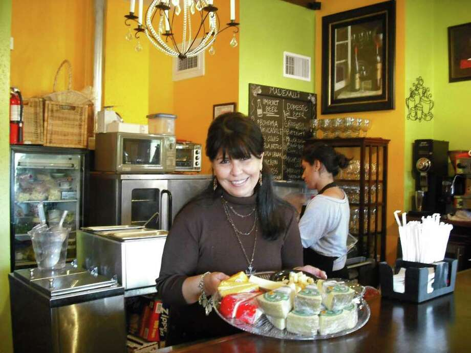 Mary Jane Morales-Salgado shows off a sample of cheeses that she sells at Madexalli Cultural Coffee Bar. The coffeehouse/bar at The Alley on Bitters offers also fair trade/organic coffee, tea, pastries along with art and music. Photo by Edmond Ortiz Photo: Photos By Edmond Ortiz