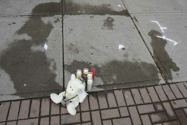 A makeshift memorial and markings on the sidewalk near 441 S. Pearl Street in Albany, N.Y. Dec. 30, 2011, are a grim reminder of a police shooting where an alleged wanted man was shot by police last evening.    ( Skip Dickstein/Times Union) Photo: Skip Dickstein / 2011