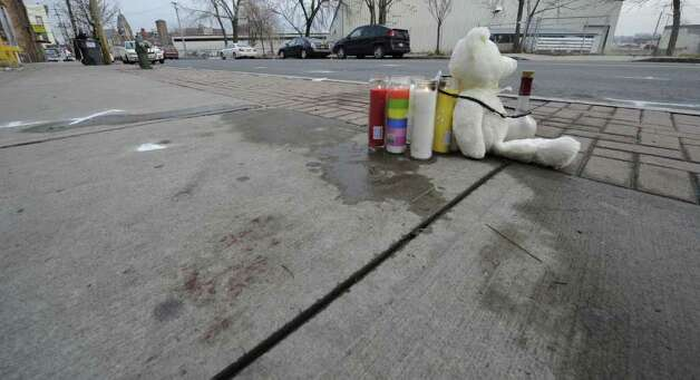 A makeshift memorial, police markings and blood stains on the sidewalk near 441 S. Pearl Street in Albany, N.Y. Dec. 30, 2011, are a grim reminder of a police shooting where an alleged wanted man was shot by police last evening.    ( Skip Dickstein/Times Union) Photo: Skip Dickstein / 2011