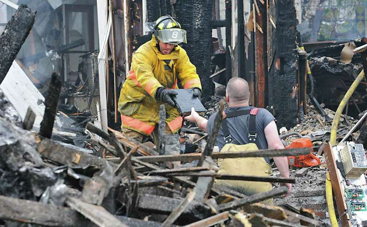 Firefighter Dave Tabor hands off Rev. Orth's Bible to firefighter Jim Yager in the smoldering rubble of a fire at Mayfield Central Presbyterian Church in Mayfield, N.Y. on April 28, 2011. The only part of the bible that endured water damage was the tassel. (Lori Van Buren / Times Union)