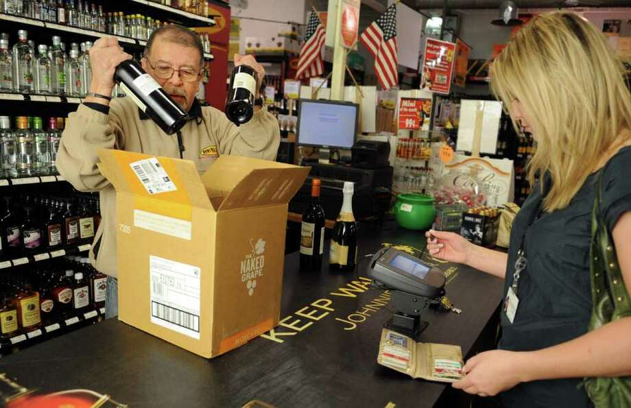 Roberto Herrera boxes some wine and champagne for Christina Doherty at Bev Max in Stamford on Friday, December 30, 2011. Photo: Lindsay Niegelberg / Stamford Advocate