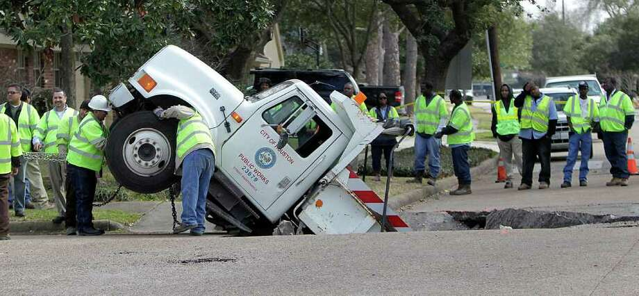 City crews work to pull a Public Works truck out of a sink hole in February 2011. A spokesman said a damaged water main had  eroded the soil under the street, which collapsed as the 7-ton truck carrying asphalt was backing up. ( Karen Warren / Houston Chronicle ) Photo: Karen Warren / Houston Chronicle