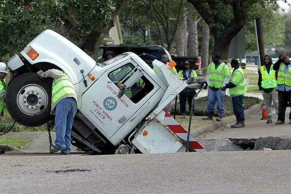 CREDIT : CREDIT LEAD-IN: Feb. 8, 2011 | City crews work to attach chains on a City of Houston Public Works dump truck, after it fell into a sink hole caused by a cave-in on Balmforth at Dumfries near Godwin Park, Tuesday, Feb. 8, 2011, in Houston. Officials said the truck was carrying gravel to repair potholes on the street when the road fell out beneath the truck, which  fell into the hole backwards. No injuries were reported and the truck was later lifted out by a large crane. ( Karen Warren / Houston Chronicle )