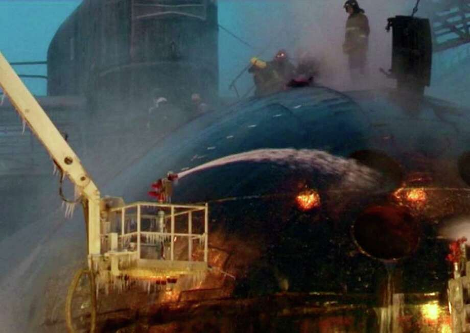 ASSOCIATED PRESS/RU-RTR TELEVISION BLAZE: Firefighters spray water on the Yekaterinburg nuclear submarine at the Roslyakovo shipyard on Friday. / RU-RTR Russian State Channel via