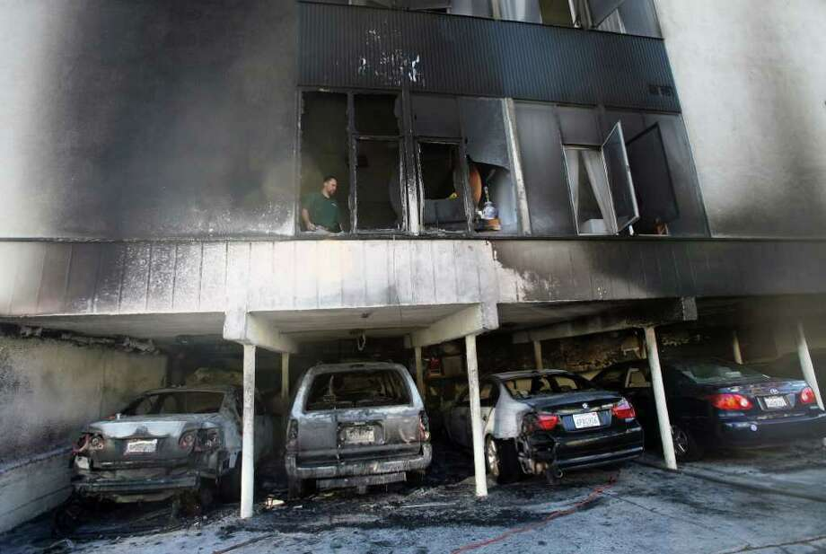 RINGO H.W. CHIU : ASSOCIATED PRESS HOLLYWOOD BURNS: An investigator works after an apartment fire in Hollywood. An arsonist torched car after car Friday, causing more than dozen blazes across Hollywood. Photo: Ringo H.W. Chiu / AP Photo/Ringo H.W. Chiu