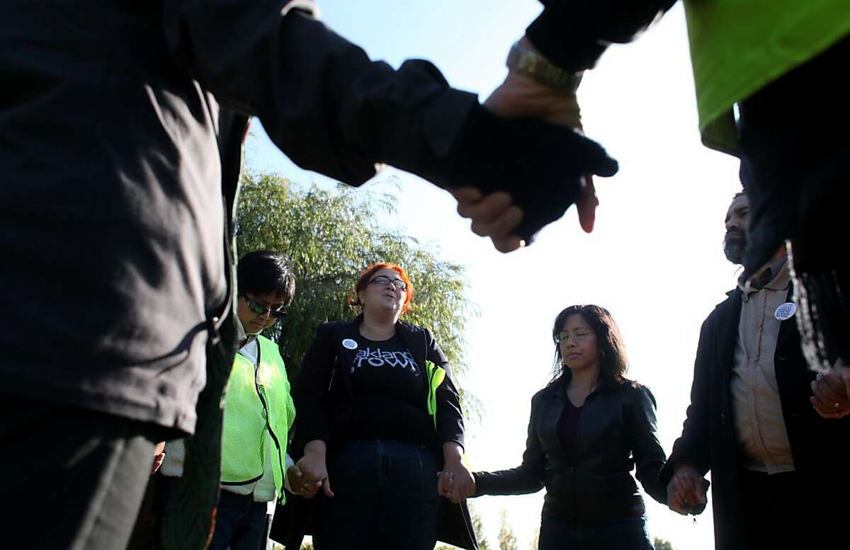 Nikki Forunato Bas, right, Executive Director of the East Bay Alliance For a Sustainable Economy, EBASE, prays with members of the clergy before talking with truck drivers as they wait in-line at the Port of Oakland, Thursday December 8, 2011, in Oakland, Calif. EBASE, is a non-profit that helps with economic and benefit discrepancies of low-income families.