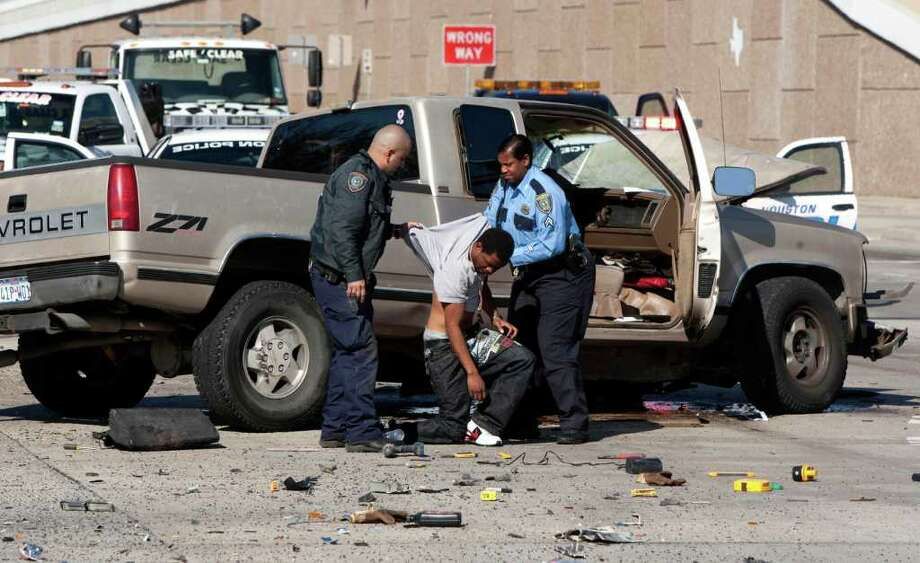 Jan. 25, 2011 | A police officers help a stolen vehicle suspect to his feet following an accident that was a result of a police chase at the intersection of Quitman and the Eastex Freeway in Houston. Photo: Brett Coomer, Houston Chronicle / © 2011 Houston Chronicle