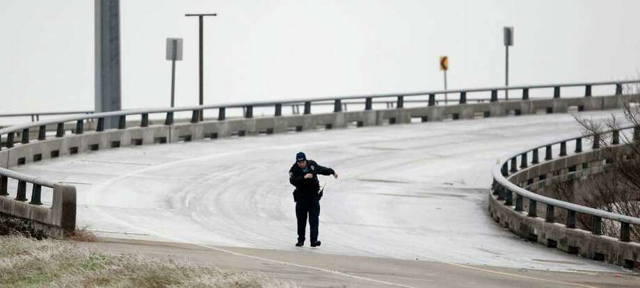 Feb. 4, 2011 | A Houston Police Department officer nearly slips as he returns to his vehicle after helping a motorist inch off an over pass connecting 610 to Hwy 59 in Houston.  A baby was born on the ice stricken bridge earlier that morning. Photo: Nick De La Torre, Houston Chronicle / © 2010 Houston Chronicle