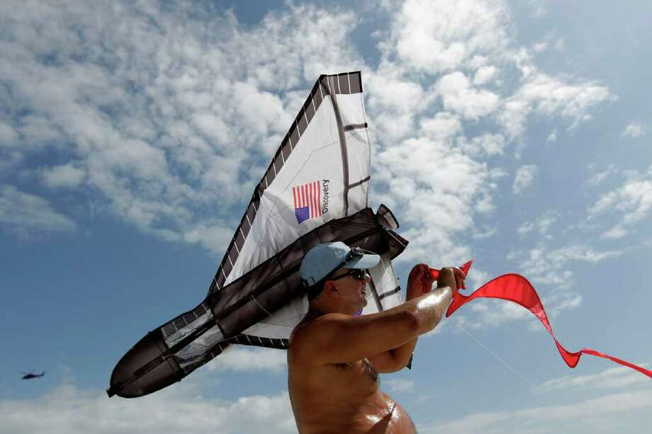 "Feb. 24, 2011 | Joseph Foti, of Poinciana, Florida, tries to untangle his space shuttle kite on the beach at Jetty Park near Cape Canaveral as people gather to watch the last Discovery shuttle launch at Kennedy Space Center. Foti said, ""In case there's a scrub, you still had a good time at this beach!"" Photo: Karen Warren, Houston Chronicle / © 2011 Houston Chronicle"