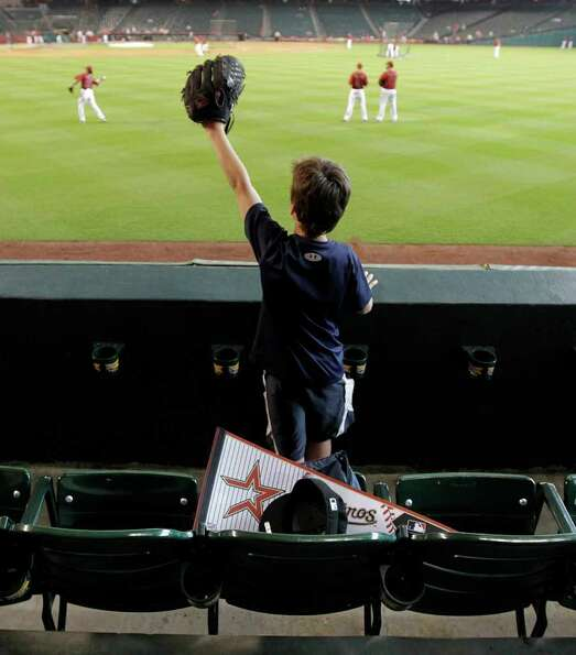 April 9, 2011 | Dylan Shoemake, 8, of Houston, waves his glove as he asks for a ball in the right fi