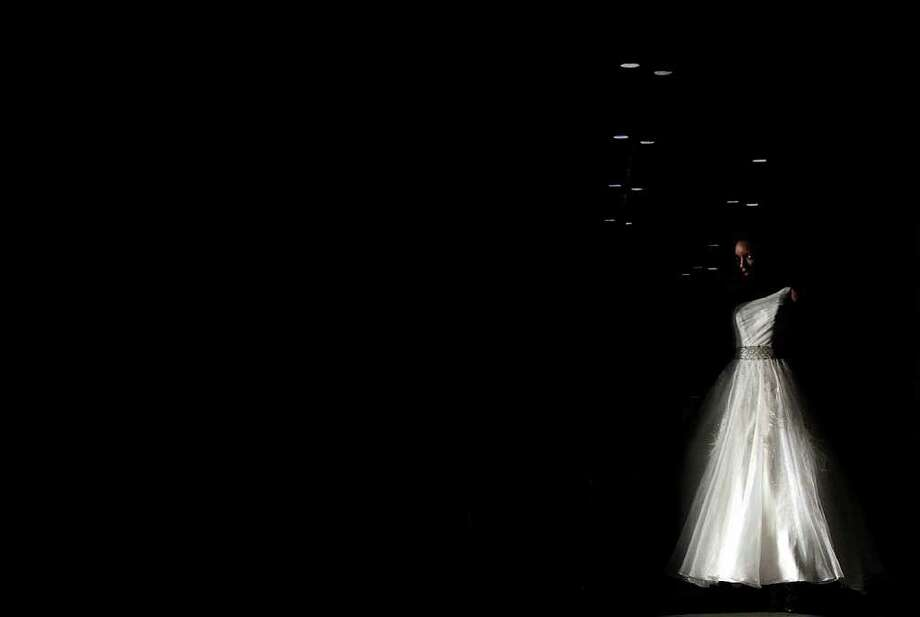 July 16, 2011 | A model enters the runway during the Impression Bridal runway show during the Bridal Extravaganza Show at the George R. Brown Convention Center in Houston. Photo: Johnny Hanson, Houston Chronicle / © 2011 Houston Chronicle