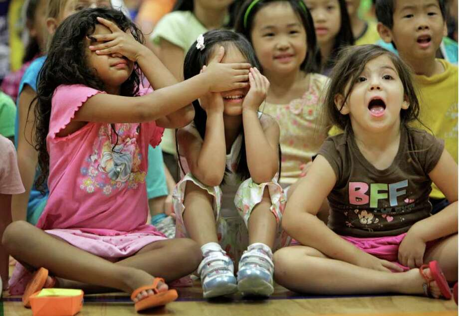 July 20, 2011 | Natalie Ramos, 5, left, covers her eyes while helping Megan Hung, 5, center, cover her eyes as they cannot bare to watch the clowns juggling so close to their front row seat during a performance by members of Clown Alley from Ringling Bros. and Barnum & Bailey at the Chinese Community Center Gymnasium in Houston. I Photo: Melissa Phillip, Houston Chronicle / © 2011 Houston Chronicle