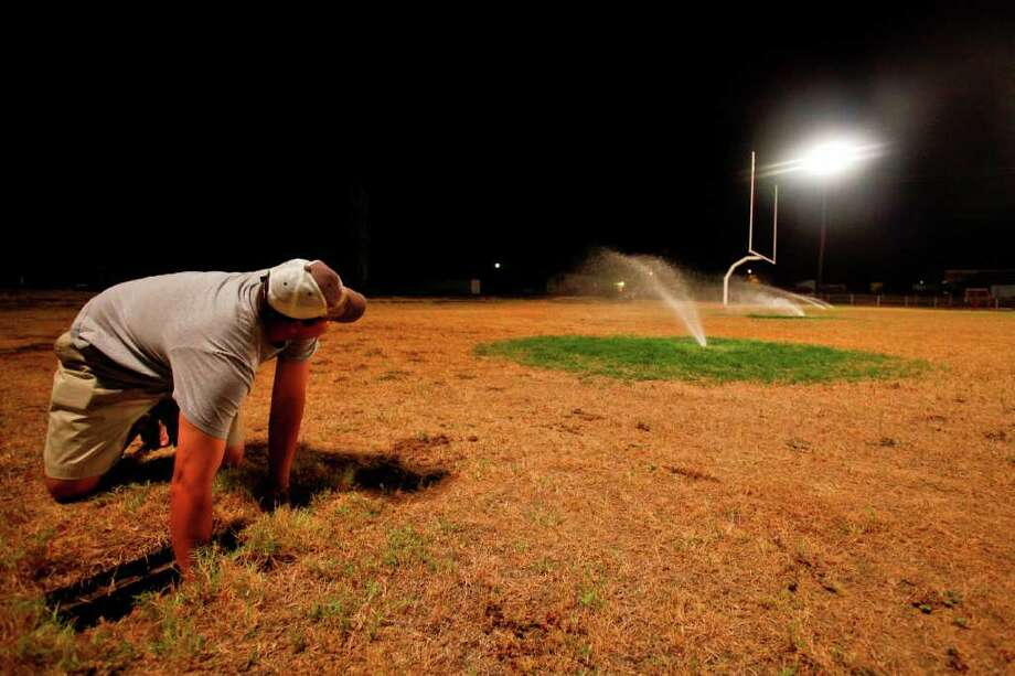 """Aug. 9, 2011   School Superintendent and Athletic Director for Robert Lee High School, Aaron Hood, adjusts the underground sprinkler system that is providing the life support for the school's' dried football field in Robert Lee. The school waters the field nightly, putting on over 6,000 gallons a day costing $200 per load of water that is trucked in from a neighboring city.  """"We take pride in our field, but it's also a matter of safety,"""" Hood said.  """"Not only for out team but for other teams when they visit, they need a semi-soft spot to fall."""" Photo: Michael Paulsen, Houston Chronicle / © 2011 Houston Chronicle"""