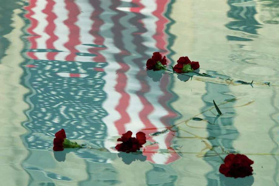 Sept. 9, 2011 | Flowers float in the reflecting pool outside City Hall during the city's 9-11 Tenth Anniversary Commemoration in Hermann Square in Houston. Photo: Brett Coomer, Houston Chronicle / © 2011 Houston Chronicle