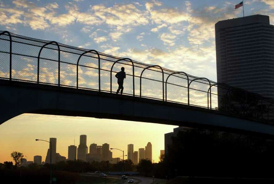 Nov. 16, 2011 | A runner uses a footbridge parallel to Jackson Hill Street to cross over Memorial Dr