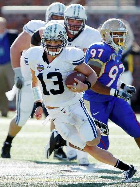 JOHN F. RHODES: ASSOCIATED PRESS STAYING ALIVE: BYU quarterback Riley Nelson, center, scrambles for a first down Friday night against Tulsa. Photo: John F. Rhodes / FR170608 AP
