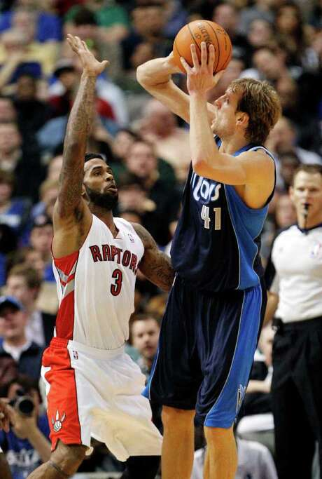Dallas' Dirk Nowitzki gets a shot up over Toronto's Gary Forbes on Friday. Photo: AP