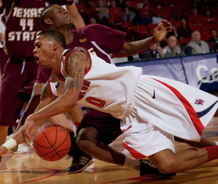 Houston's Jospeh Young (0) and Texas State's Basil Brown (22) collide as Young drives to the basket