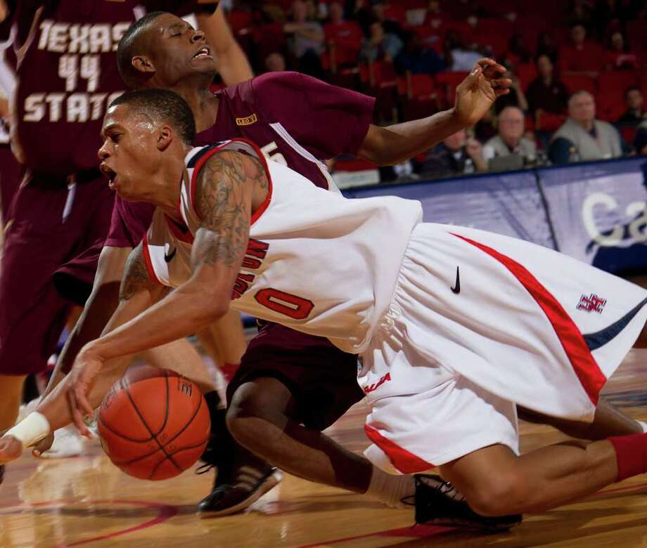 Houston's Jospeh Young (0) and Texas State's Basil Brown (22) collide as Young drives to the basket during the first half of an NCAA basketball game between Houston and Texas State Friday, December 30, 2011 in Houston. Photo: Bob Levey, Houston Chronicle / ©2011 Bob Levey