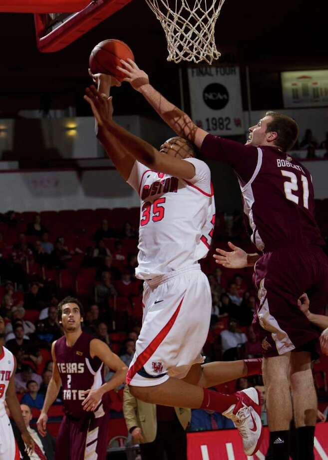 Houston's TaShawn Thomas (35) has his shot blocked by Texas State's Matt Staff (21) during the first half of an NCAA basketball game between Houston and Texas State Friday, December 30, 2011 in Houston. Photo: Bob Levey, Houston Chronicle / ©2011 Bob Levey
