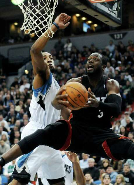 Miami's Dwyane Wade goes for a reverse layup against Minnesota's Derrick Williams. Photo: AP