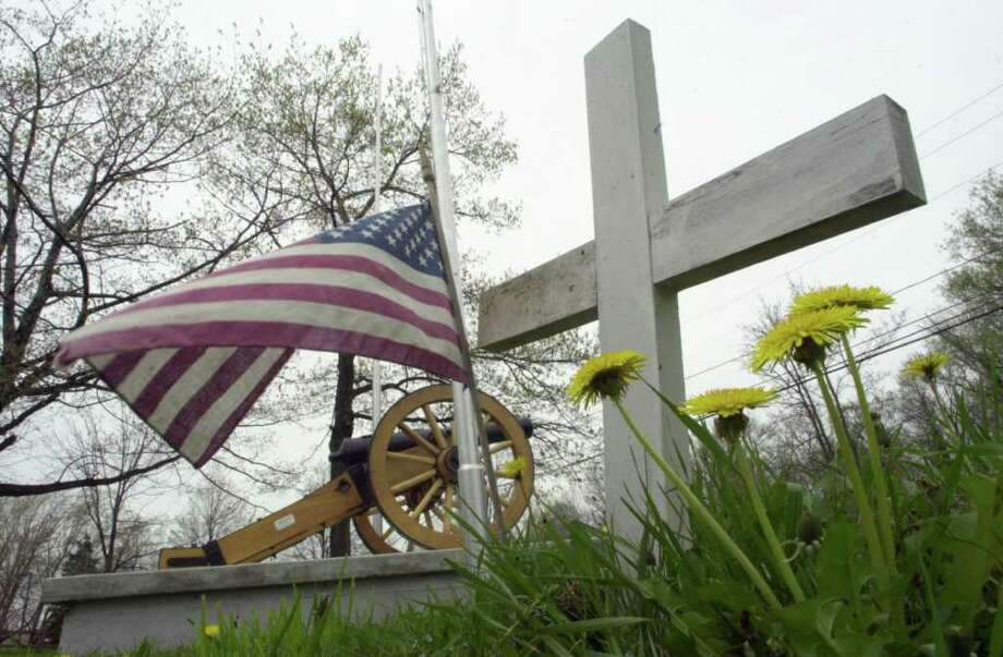 A flag blows in the breeze next to a grave marker in the War of 1812 Cemetery in Cheektowaga, N.Y., Wednesday, May 8, 2002. Town officials say they have sufficient evidence to conclude that the cemetery contains the remains of several hundred War of 1812 soldiers. Now the town is seeking to have the suburban Buffalo cemetery placed on the National Register of Historic Places. (AP Photo/David Duprey) Photo: DAVID DUPREY / AP