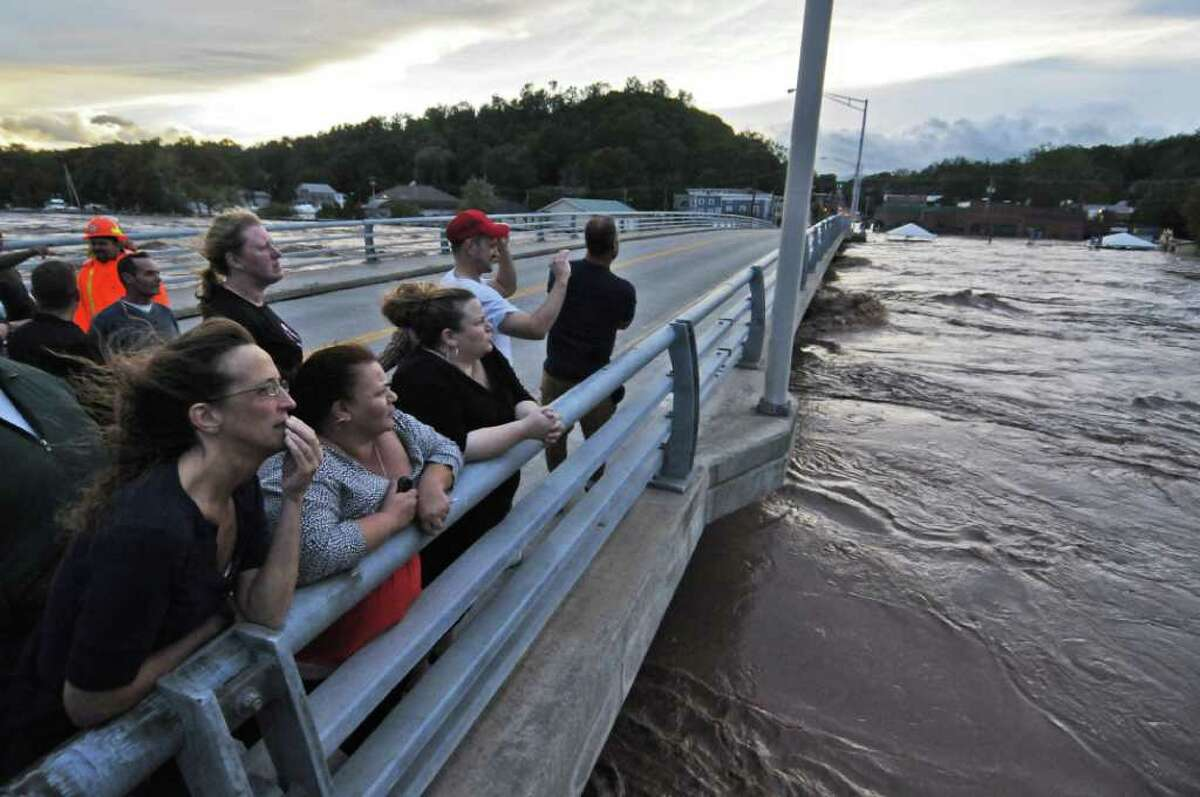Cathy Bridges, lower left with hand on lips, Ronnie Higgins, center, and her sister Makenzie Higgins, all of Catskill, stand on Bridge Street as they watch the raging waters of the Catskill Creek pass underneath, swollen as a result of Hurricane Irene on Sunday Aug. 28, 2011, in Catskill, NY. (Philip Kamrass / Times Union archive)
