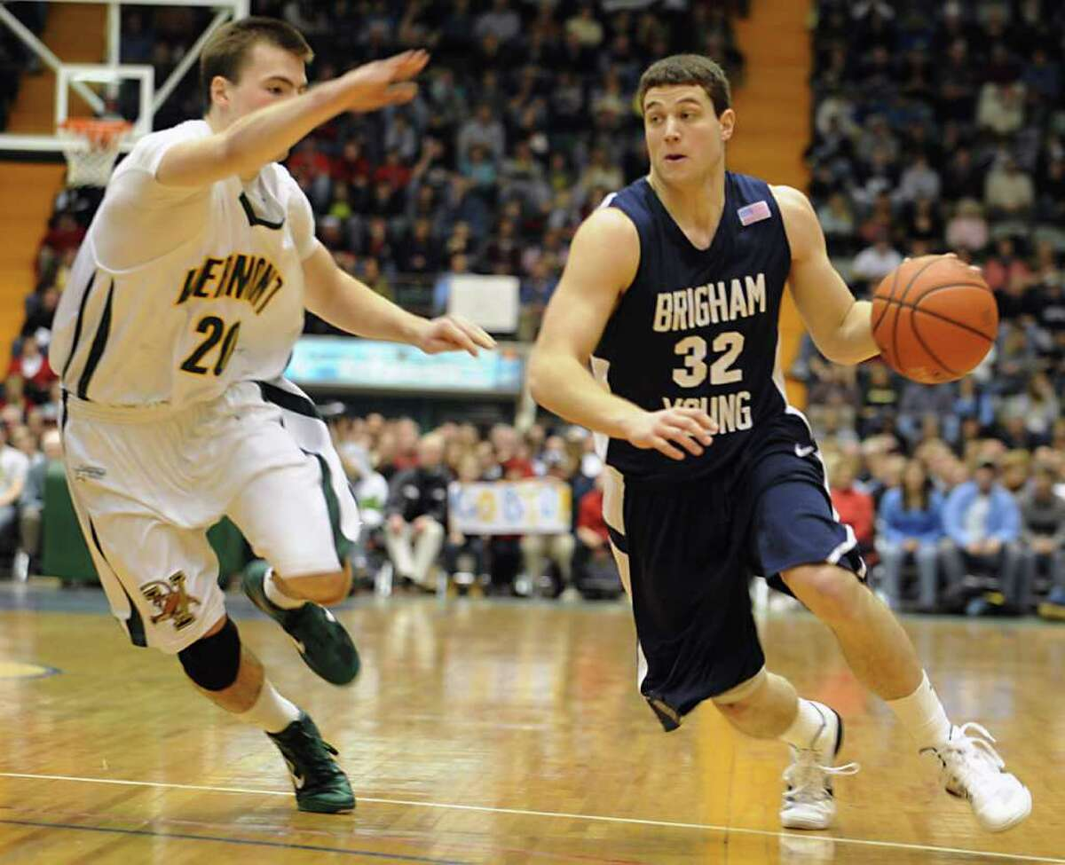 Jimmer Fredette, of BYU, drives against Brendan Bald, of Vermont, during a basketball game at the Glens Falls Civic Center in Glens Falls, NY. Jimmer is a graduate of Glens Falls. (Lori Van Buren / Times Union)