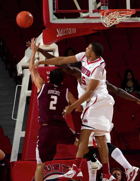 BOB LEVEY: FOR THE CHRONICLE SWAT TEAM: UH's TaShawn Thomas, right, blocks a shot by Texas State's Brooks Ybarra on Friday night. Photo: Bob Levey / ©2011 Bob Levey