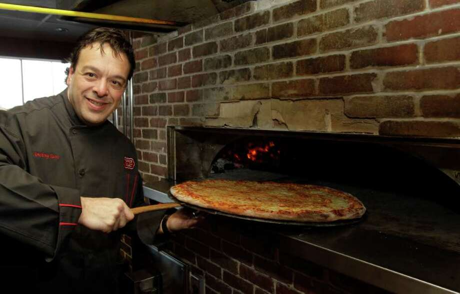 MELISSA PHILLIP PHOTOS : CHRONICLE A NICE ROUND MEAL: Franchise owner Anthony Russo pulls a pie from the oven at the Russo's Coal-Fired Italian Kitchen location on the Northwest Freeway. Photo: Melissa Phillip / © 2011 Houston Chronicle