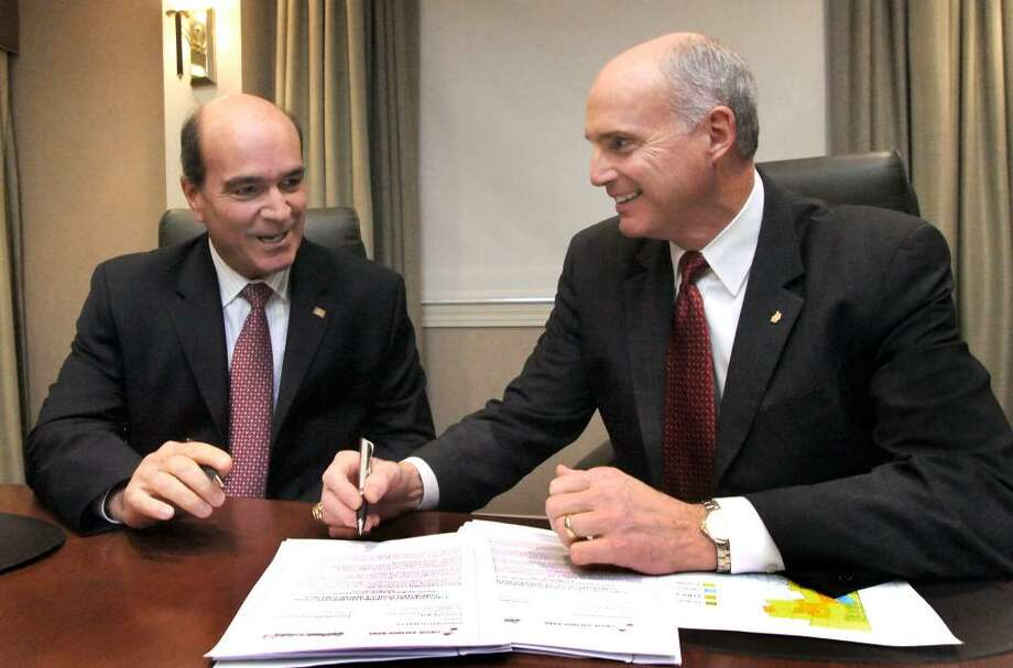 Joseph Greco, Pres. & CEO, First Litchfield Financial Corp., left, and John Kline, Pres & CEO Union Savings, signing documentation for the purposed merger of the two banks in the Boardroom of the Union Savings Bank in Danbury, on Monday, Oct.26,2009. Photo: Michael Duffy / The News-Times
