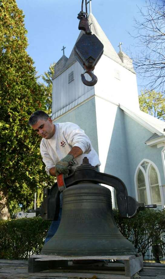 John Fernandes, of A & A Crane and Rigging in Bridgeport, unhooks the historic turn of the century church bell from his crane at Holy Trinity Greek Orthodox  Church on Hubbell Avenue in Ansonia, Monday, Oct. 26, 2009. Photo: Phil Noel / Connecticut Post