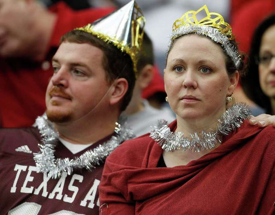 Matthew Herring, Texas A&M class of '01, with his wife, Melissa Herring (class of '02) with their New Years Eve hats on during the first quarter of the Meineke Car Care Bowl at Reliant Stadium,Saturday, Dec. 31, 2011, in Houston. Photo: Karen Warren, Houston Chronicle / © 2011 Houston Chronicle