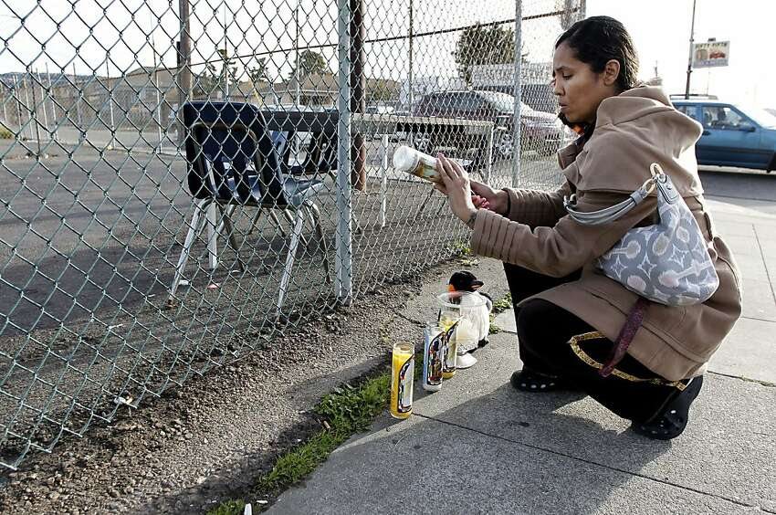 Dashy Scott of Union City lights a candle at the growing memorial, on Saturday December 31, 2011, for a 5-year-old boy who was shot and killed near the corner of 55th Ave. and International Blvd. in Oakland, Ca. last night.
