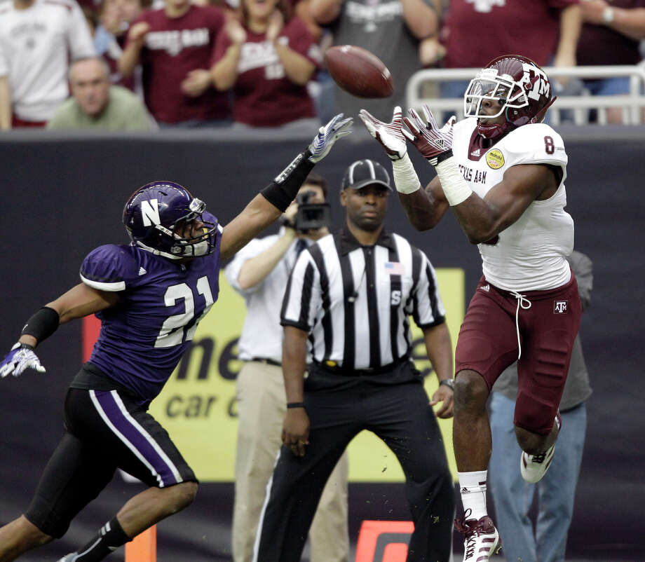 Texas A&M wide receiver Jeff Fuller (8) catches a touchdown pass as Northwestern cornerback Mike Bolden (21) defends during the second quarter of the  Car Care Bowl NCAA college football game Saturday, Dec. 31, 2011, in  Houston. (AP Photo/David J. Phillip) / AP2011