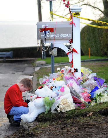 Riley Fitzpatrick, 7, says a prayer for the Badger family in front of 2267 Shippan Ave. in Stamford on Saturday, December 31, 2011. Photo: Lindsay Niegelberg / Stamford Advocate