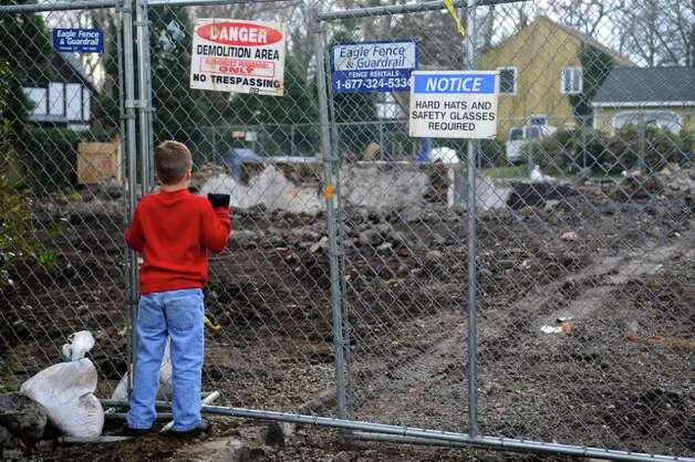 Riley Fitzpatrick, 7, looks through a fence to the remains of the demolished house at 2267 Shippan Ave. in Stamford on Saturday, December 31, 2011. Photo: Lindsay Niegelberg / Stamford Advocate