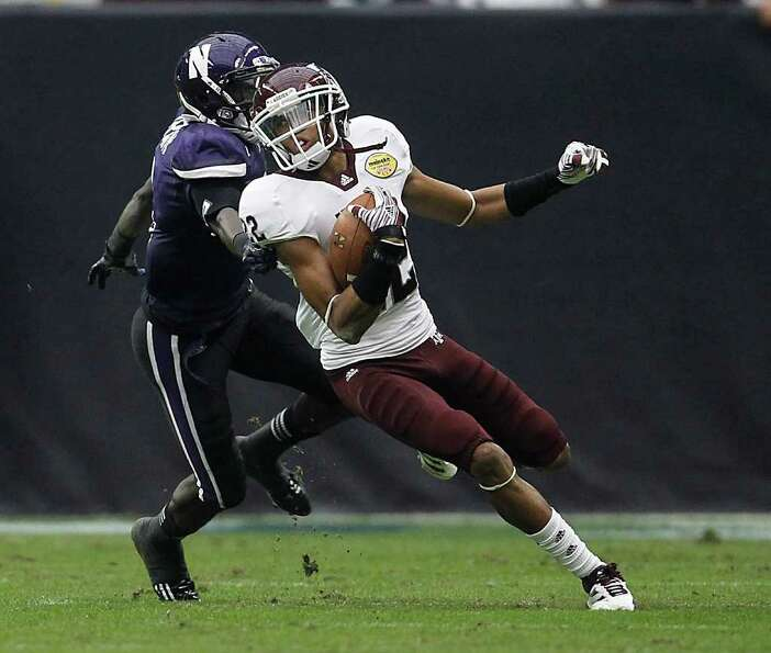 Texas A&M Aggies defensive back Dustin Harris (22) runs the ball against the defense of Northwestern