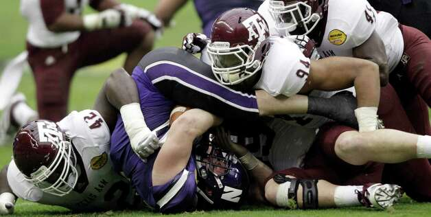 Northwestern running back Jacob Schmidt, center, is crushed by Texas A&M's Kirby Ennis (42), Damontre Moore (94), and Steven Jenkins (45) during the first quarter of the Car Care Bowl NCAA college football game Saturday, Dec. 31, 2011, in Houston. Photo: David J. Phillip, AP / AP