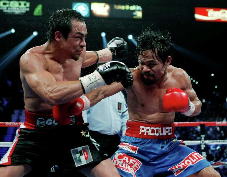 JAE C. HONG : ASSOCIATED PRESS FILE EMBLEM: Juan Manuel Marquez, left, sporting the Institutional Revolutionary Party's PRI logo on his trunks, takes a hit from Filipino fighter Manny Pacquiao in Las Vegas on Nov. 12. Photo: Jae C. Hong / AP