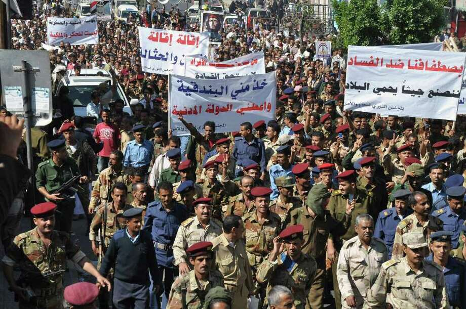 "Yemeni soldiers and officers march  during a rally demanding reforms and dismissal of a senior official over alleged corruption in Taiz, Yemen, Saturday, Dec. 31, 2011. Arabic on the banners, center, reads, ""take from me the rifle and give me the civil state,"" and at right, ""with our standing against corruption, we will build army to protect the country."" The son of Yemen's outgoing president is leading a crackdown to purge the Republican Guard, which he commands, of any rebellious officers found to be siding with anti-government protesters, a military official said Saturday. (AP Photo/Anees Mahyoub) Photo: Anees Mahyoub / AP"