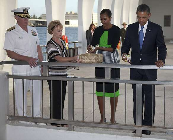 President Barack Obama, right, and first lady Michelle Obama, second from right, take flowers to drop into the water at the USS Arizona Memorial, part of the World War II Valor in the Pacific National Monument, with Admiral Robert Willard and his wife Donna Willard, left, Thursday, Dec. 29, 2011, in Pearl Harbor, Hawaii. (AP Photo/Carolyn Kaster) Photo: Carolyn Kaster, Associated Press