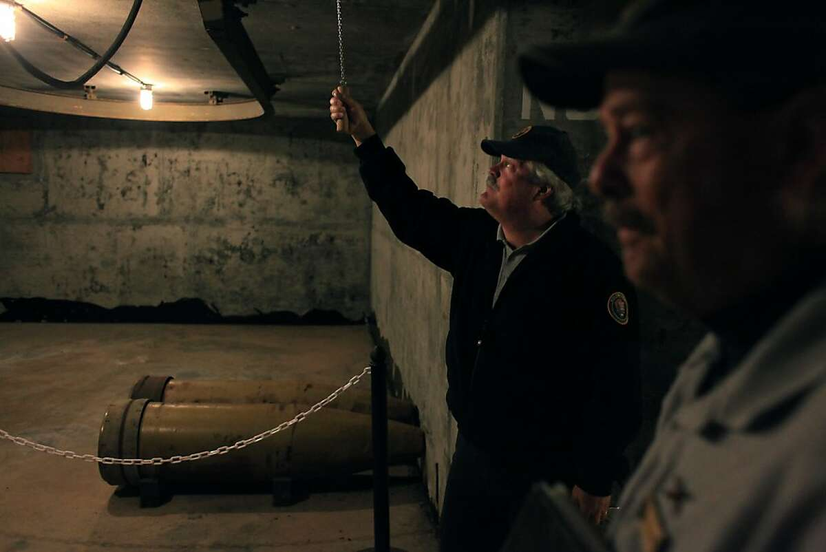 National Park Service volunteer John Martini (left) operates a chain used to shift the tracks to move ammunition, next to an ammunition niche at Battery Townsley in the Marin Headlands on Wednesday, December 14, 2011 in Sausalito, Calif.