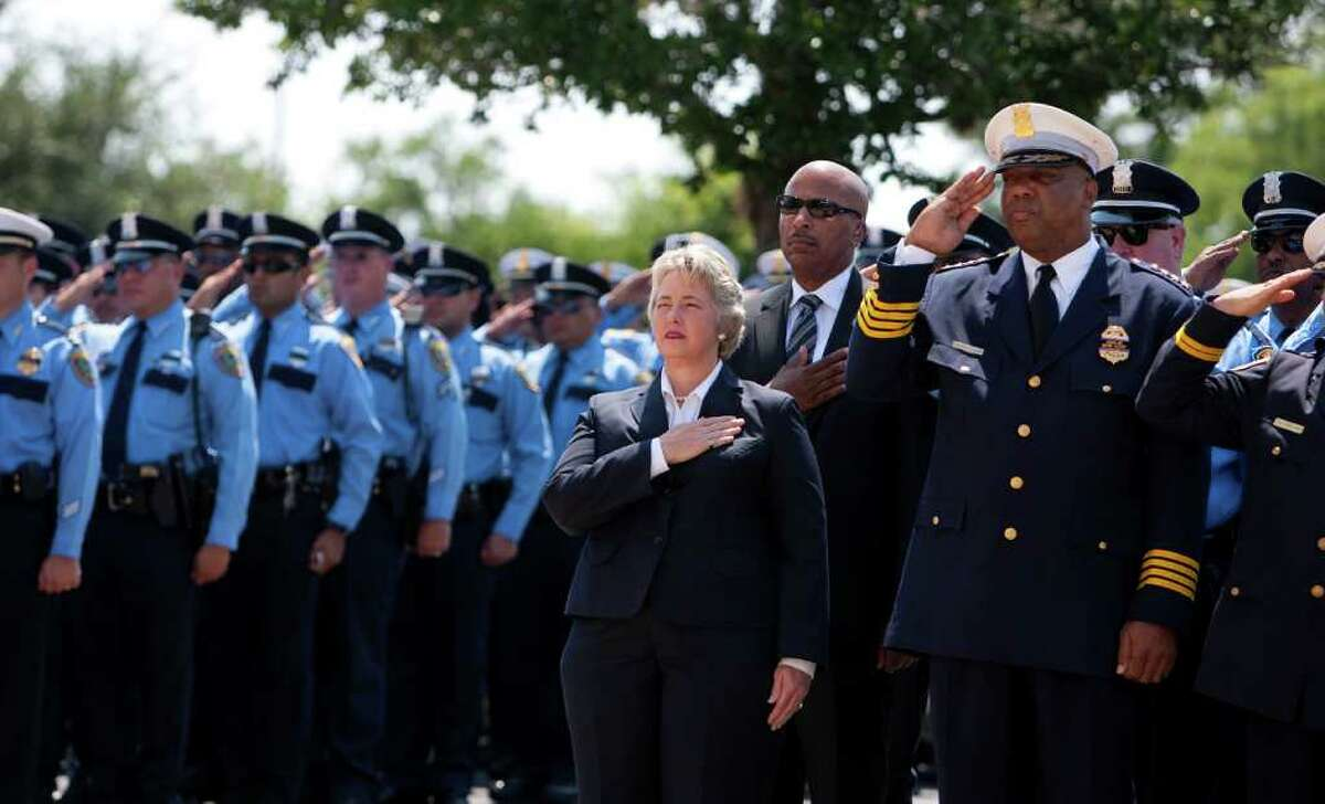 Houston Mayor Annise Parker and Police Chief Charles McClelland salute during a ceremony after the funeral of police officer Kevin Will on June 2.