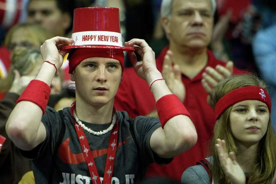 Houston Rockets fan Justin Keller dons a celebratory New Year's hat before an NBA basketball game against the Atlanta Hawks at Toyota Center on Saturday, Dec. 31, 2011, in Houston. Photo: Smiley N. Pool, Houston Chronicle / © 2011  Houston Chronicle