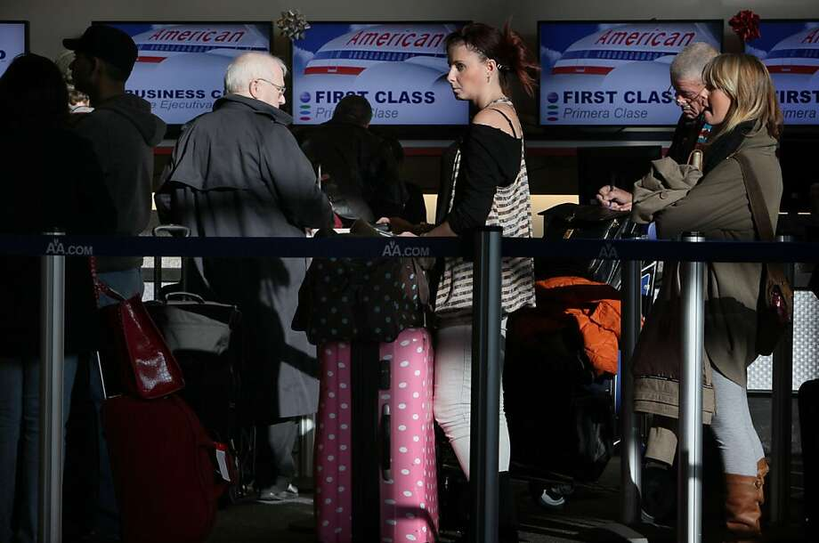 Amanda McGrath (middle) from Vancouver checks into the American Airlines ticket counter at San Francisco International Airport in South San Francisco, Calif., to fly back home after the holidays November 29, 2011. Boarding an airplane has never been safer. In the last 10 years, there were 153 fatalities in U.S. airline crashes. That's 2 deaths for every 100 million passengers and the safest decade in the country's aviation history, according to an Associated Press analysis of government accident data. Photo: Liz Hafalia, The Chronicle