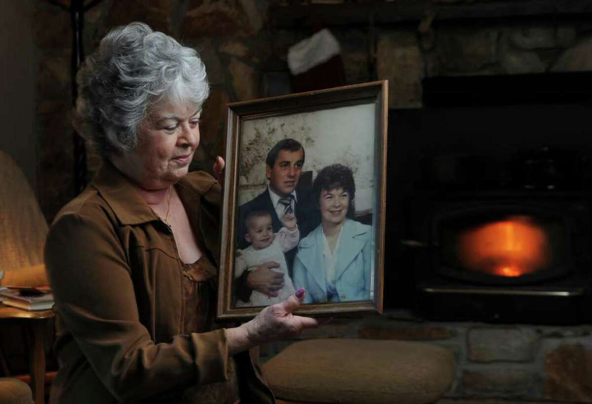 Margaret Porto LaMori holds a 1984 photograph of herself with her late husband Peter E. Porto and their grandchild Krishna, on Tuesday Dec. 13, 2011 in Scotia, N.Y. Peter died in 2006 from illness related to exposure to asbestos. (Philip Kamrass / Times Union)